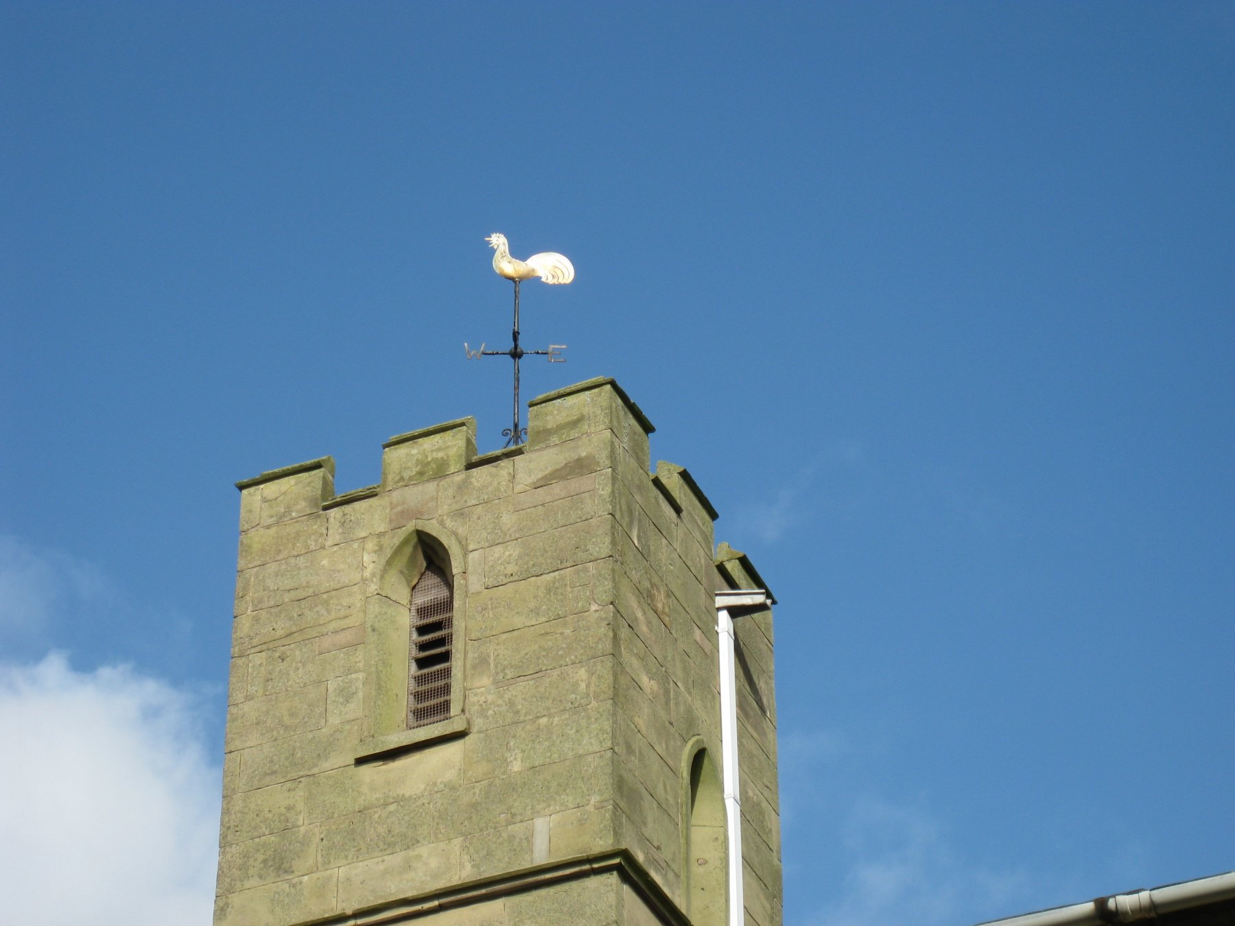 a church tower with a cockerel weather vane on top